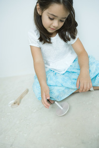 Girl sitting and playing with topの写真素材 [FYI04320215]