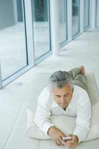 Man lying and listening to mp3 playerの写真素材 [FYI04320217]