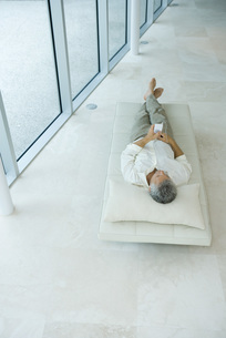 Man lying and listening to mp3 playerの写真素材 [FYI04320218]