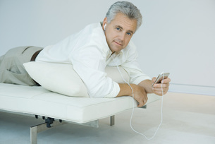 Man lying and listening to mp3 playerの写真素材 [FYI04320219]