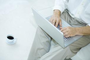 Man sitting using laptop computerの写真素材 [FYI04320222]