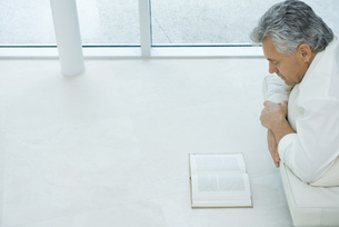 Mature man lying on stomach reading bookの写真素材 [FYI04320224]