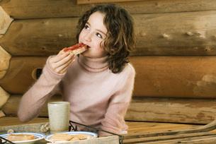Girl having snack, looking awayの写真素材 [FYI04320238]