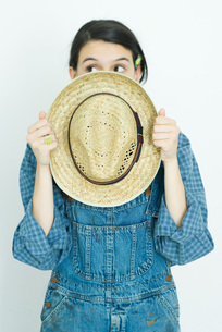 girl holding straw hat in front of faceの写真素材 [FYI04320269]
