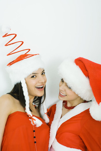 Two friends wearing Santa hatsの写真素材 [FYI04320316]