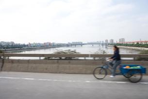 Cyclist with cart crossing bridgeの写真素材 [FYI04320358]