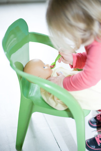 Girl pretending to feed baby dollの写真素材 [FYI04320375]