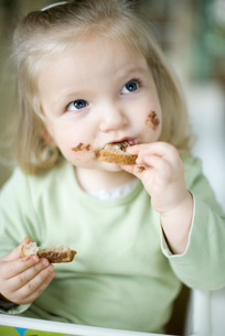 Girl eating bread with chocolateの写真素材 [FYI04320376]