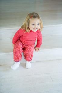 Blonde toddler girl sitting on stepsの写真素材 [FYI04320378]