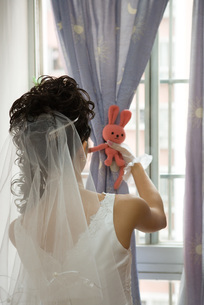 Bride tying curtain with stuffed toyの写真素材 [FYI04320426]