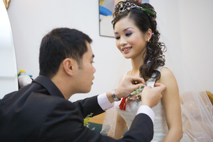Groom pinning corsage on bride's dressの写真素材 [FYI04320430]