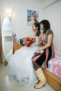 Bride sitting on bed with friendの写真素材 [FYI04320436]