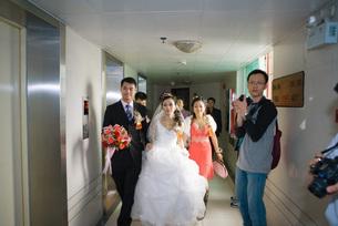 Bride and groom walking through hallwayの写真素材 [FYI04320451]