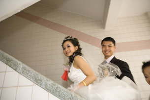 Bride and groom walking up stairsの写真素材 [FYI04320467]
