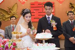 Newlyweds standing next to wedding cakeの写真素材 [FYI04320484]