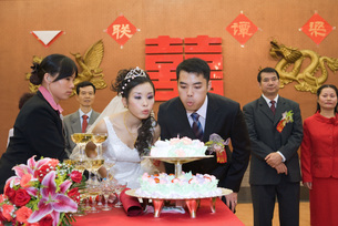 Newlyweds blowing out candle on cakeの写真素材 [FYI04320486]