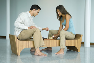 Couple sitting on bench at chess boardの写真素材 [FYI04320491]