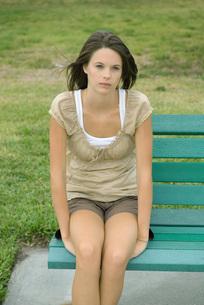 Teenage girl sitting on benchの写真素材 [FYI04320502]
