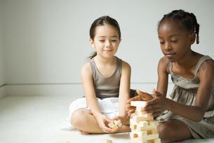 Two girls sitting and stacking blocksの写真素材 [FYI04320514]