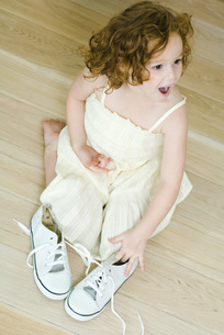 Girl kneeling near pair of shoesの写真素材 [FYI04320534]