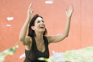 Woman raising armsの写真素材 [FYI04320575]