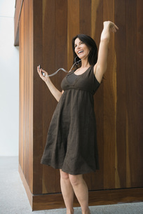 Woman listening to MP3 player, dancingの写真素材 [FYI04320577]