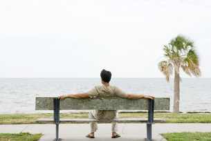 Man sitting on bench, facing oceanの写真素材 [FYI04320581]