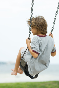 Barefoot boy on swing, rear viewの写真素材 [FYI04320591]
