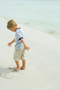 Boy standing and digging toes into sandの写真素材 [FYI04320596]