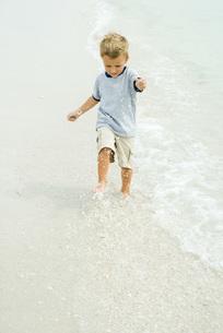 Little boy splashing in surf on beachの写真素材 [FYI04320597]