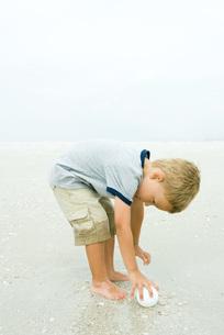 Boy bending over to pick up ballの写真素材 [FYI04320599]