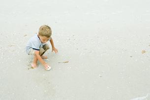 boy squatting, picking up ball on beachの写真素材 [FYI04320600]