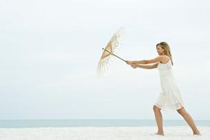 Woman holding parasol on beachの写真素材 [FYI04320604]