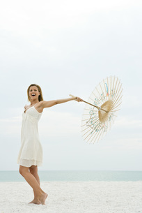 Woman holding parasol on beachの写真素材 [FYI04320605]