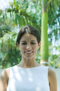 Woman smiling, palm trees in backgroundの写真素材 [FYI04320737]