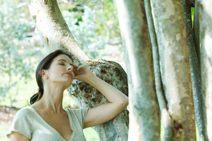 Woman leaning against tree trunkの写真素材 [FYI04320739]