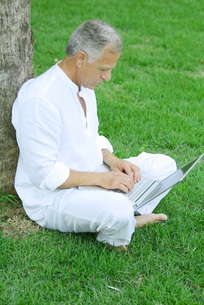 Man sitting and using laptop computerの写真素材 [FYI04320744]