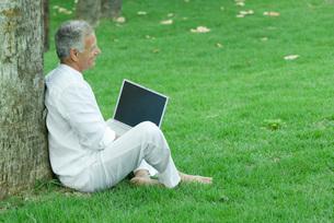 Man sitting and using laptop computerの写真素材 [FYI04320746]