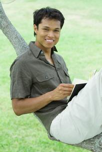 Man resting on tree branch, holding bookの写真素材 [FYI04320752]