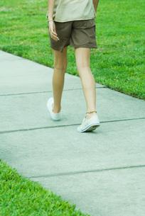 Female walking on sidewalk, waist downの写真素材 [FYI04320773]