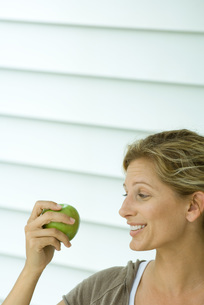 Woman holding up apple and smilingの写真素材 [FYI04320775]
