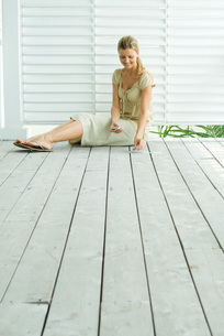 Woman sitting on deck playing solitaireの写真素材 [FYI04320778]