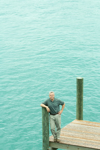 Man standing on dock, leaning on postの写真素材 [FYI04320791]