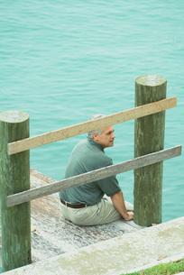 Man sitting on edge of dockの写真素材 [FYI04320792]