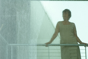 Woman looking through window in rainの写真素材 [FYI04320793]