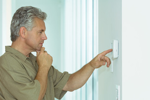 Man looking at control panel on wallの写真素材 [FYI04320794]
