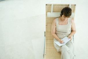 Woman sitting and writing in diaryの写真素材 [FYI04320798]