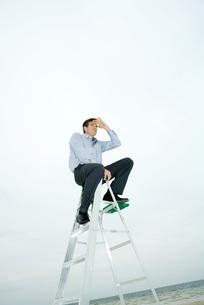 Man sitting on top of ladderの写真素材 [FYI04320812]