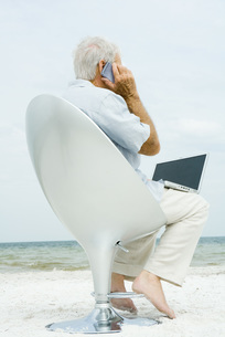 man using laptop and cell phone on beachの写真素材 [FYI04320813]
