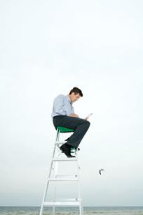 Man sitting on top of ladderの写真素材 [FYI04320815]